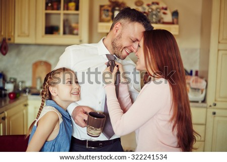 Happy couple and their daughter in the kitchen - stock photo