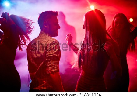 Happy couple and their friends dancing in disco club - stock photo