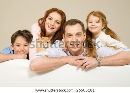 Happy couple and their two children smiling with pet among them