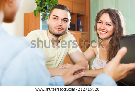 Happy couple answer questions of outreach worker with laptop at table in office - stock photo