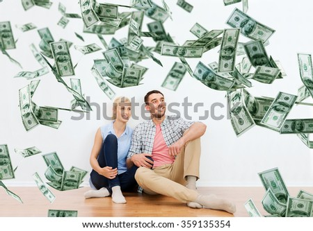 happy couple at home over dollar money falling - stock photo