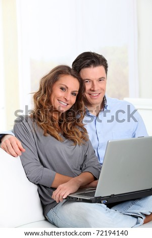 Happy couple at home with laptop computer