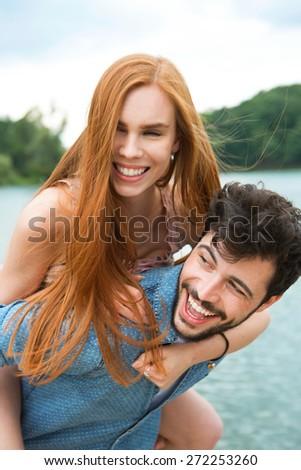 Happy couple at lake, man carrying girlfriend piggyback - stock photo