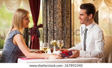 Happy couple at restaurant, boyfriend is giving present to his girlfriend - stock photo