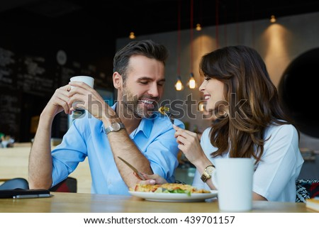 Happy couple at restaurant eating lunch, having fun