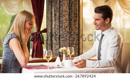 Happy couple at restaurant, man is proposing his girlfriend - stock photo