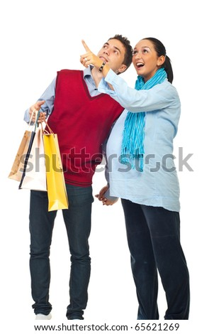 Happy couple at shopping ,pregnant wife showing something to her husband and pointing up isolated on white background - stock photo