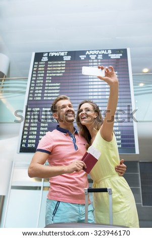 Happy couple at the airport makes selfie - stock photo