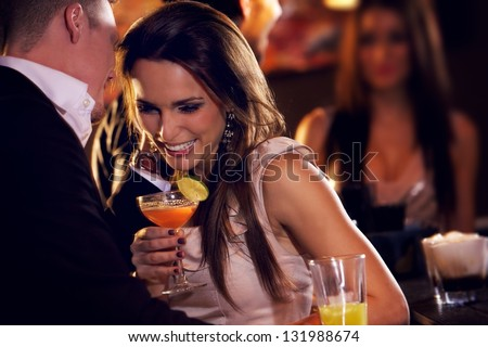 Happy couple at the bar enjoying the cocktail party - stock photo