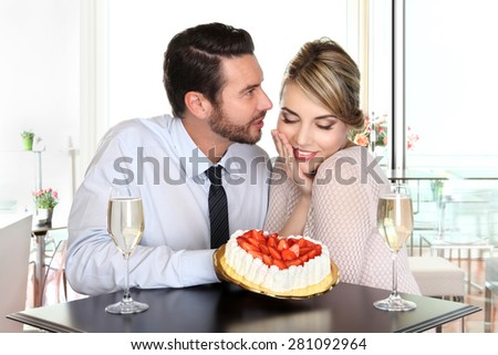 happy couple at the bar with sparkling wine and cake, love concept - stock photo