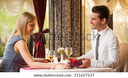 Happy couple at the restaurant, man is giving present to his girlfriend