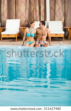 Happy couple at the swimming pool - stock photo