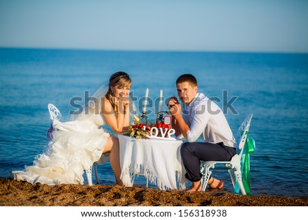 happy couple at the table by the sea. looking at the camera