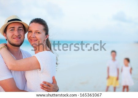 Happy couple at tropical beach with two kids standing on background
