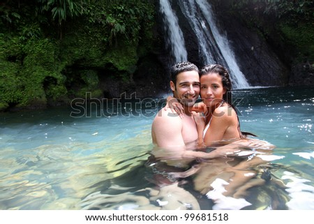 Happy couple bathing near waterfall in island