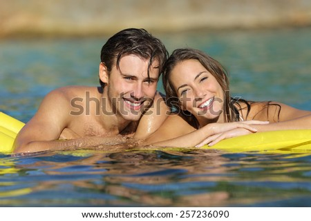 Happy couple bathing on the beach in summer vacation with a perfect white smile and looking at camera - stock photo
