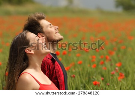 Happy couple breathing fresh air in a colorful field with red poppy flowers - stock photo