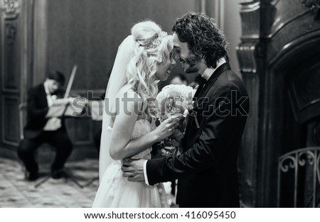 Happy couple, bride & groom hugging at luxury wedding ceremony aisle b&w