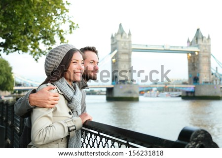 Happy couple by Tower Bridge, River Thames, London. Romantic young couple enjoying view during travel. Asian woman, Caucasian man in London, England, United Kingdom. - stock photo