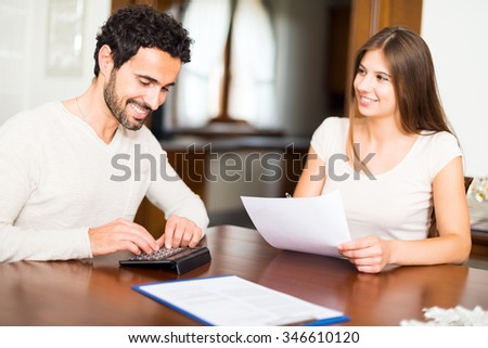 Happy couple calculating their expenses together - stock photo