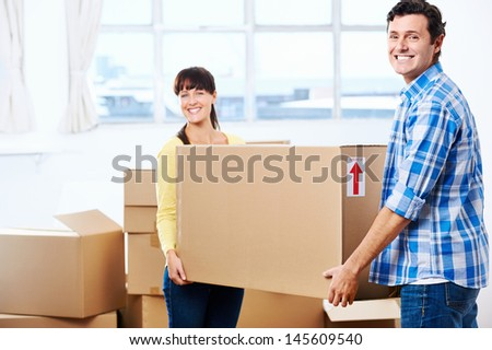 Happy couple carrying boxes moving into new home apartment house