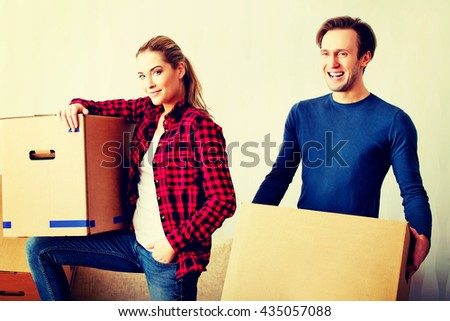 Happy couple carrying cardboard boxes in new home - stock photo