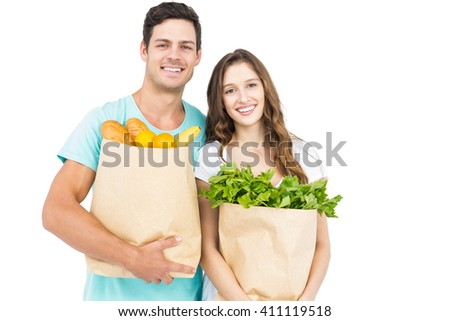 Happy couple carrying grocery bags on white background - stock photo