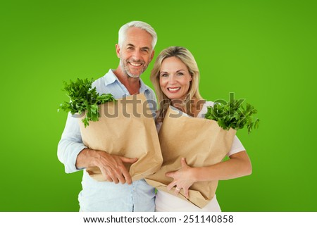 Happy couple carrying paper grocery bags against green vignette