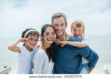 happy couple carrying their kids on their back in front of the sea - stock photo