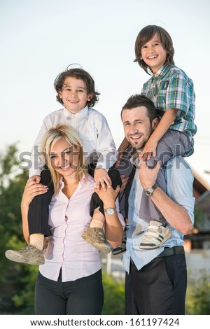 Happy couple carrying two kids on shoulders outdoors - stock photo