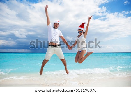 Happy couple celebrating Christmas on beach, jumping in the air