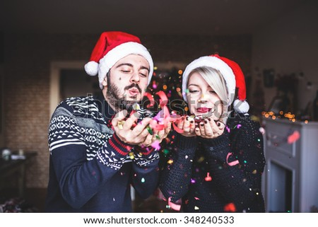 Happy couple celebrating xmas,blowing up confetti, Christmas, New Year