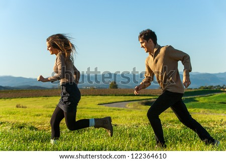Happy couple chasing each other in countryside. - stock photo