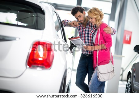 Happy couple chooses to buy a car in showroom - stock photo