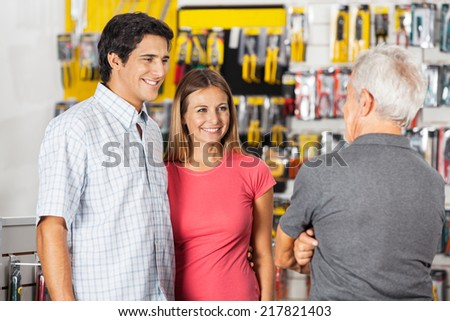 Happy couple conversing with senior man in hardware store