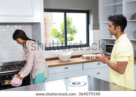 Happy couple cooking biscuits in the oven at home - stock photo