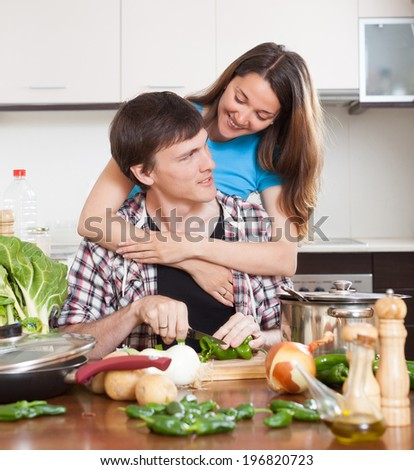 Happy couple cooking in domestic kitchen