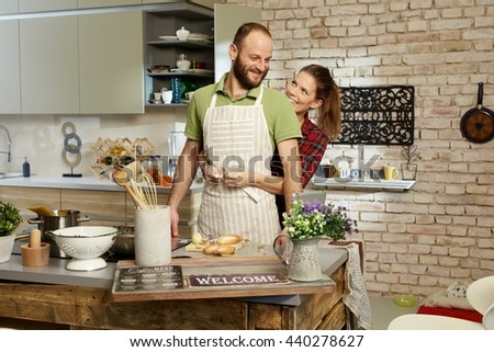 Happy couple cooking together in kitchen, woman tieing apron on man.