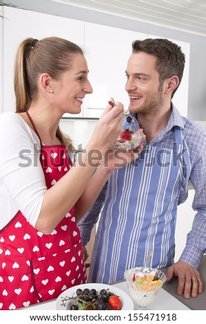 Happy couple cooking together in the kitchen. - stock photo
