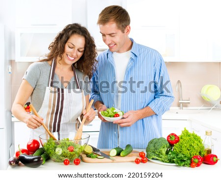 Happy Couple Cooking Together - Man and Woman in their Kitchen at home Preparing Dinner - Vegetable Salad. Diet. Dieting. Healthy vegetarian food, vegan. Family cooking together at home - stock photo