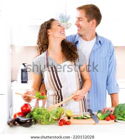 Happy Couple Cooking Together - Man and Woman in their Kitchen at home Preparing Vegetable Salad.Diet.Dieting. Healthy Food. Vegan food concept - stock photo