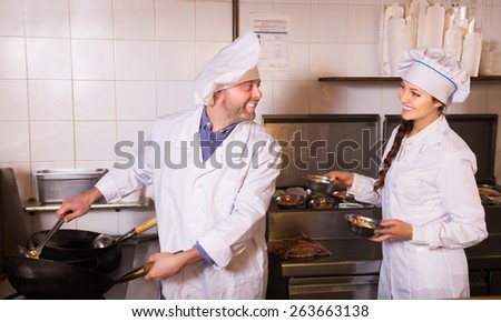 Happy couple cooks greeting customers at bistro kitchen - stock photo