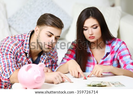 Happy couple counting money from the moneybox - stock photo