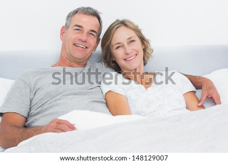 Happy couple cuddling in bed looking at camera at home in bedroom