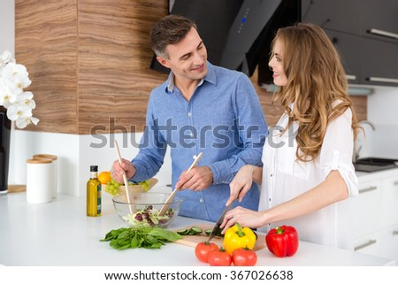 Happy couple cutting vegetables and making salad on the kitchen together - stock photo