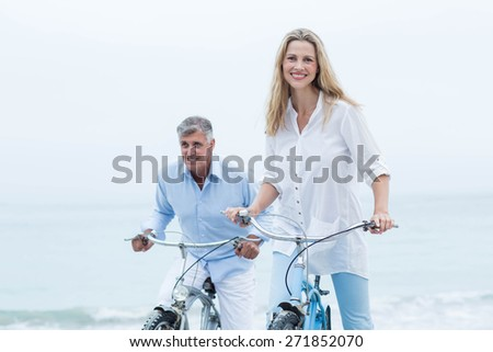 Happy couple cycling together at the beach - stock photo
