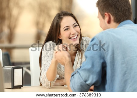 Happy couple dating and flirting and holding hands together in a coffee shop with a sunset light outdoor in the background - stock photo