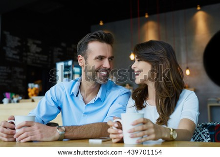 Happy couple dating at cafe, looking at each other