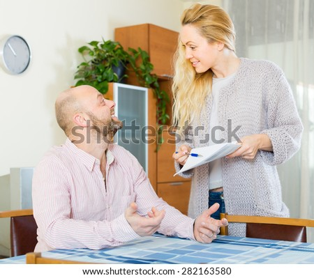 Happy couple discussing details of marriage settlement indoors. Focus on man - stock photo