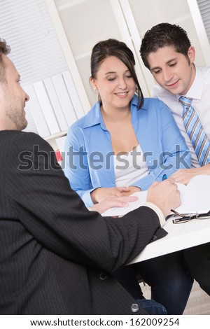Happy couple discussing future financial plans with consultant at office  - stock photo